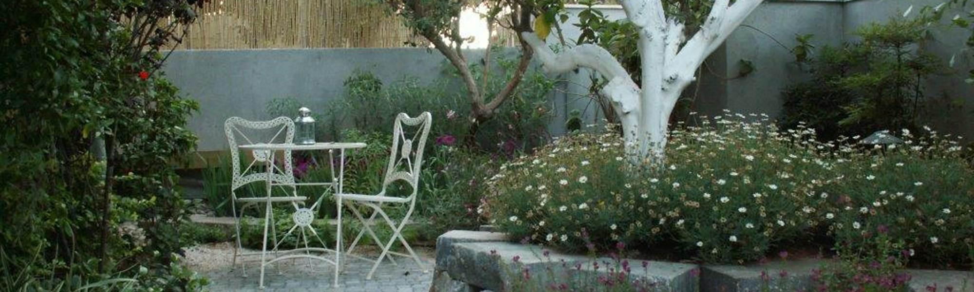 גינה מעוצבת עם כיסאות ברזל לבנים