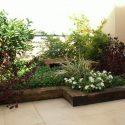 גינה מעוצבת עם אדניות עץ ופרחים