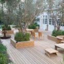 עיצוב מתחם חיצוני בשילוב דק עצים ושולחנות ישיבה