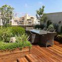 גינת גג גדולה עם אדניות עץ ושולחן חום